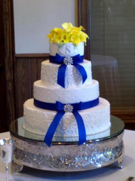 [Image: Wedding cake topped with yellow callas]